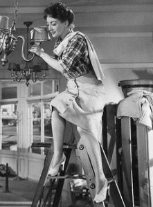 Mildred wears a mixture of masculine and feminine clothing while getting her restaurant ready. © 1945 – Warner Bros. All Rights Reserved.