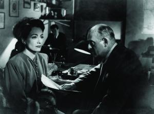 Mildred is questioned in shadow. © 1945 – Warner Bros. All Rights Reserved.
