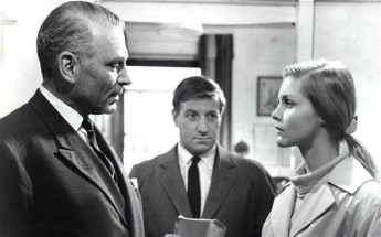 Many of the shots in the film make use or corners or tripod arrangements, but the lens makes them look flat, like here, where Newhouse and Ann's conversation almost looks to be cut in half by another police officer. © 1965 – Columbia Pictures. All Rights Reserved.